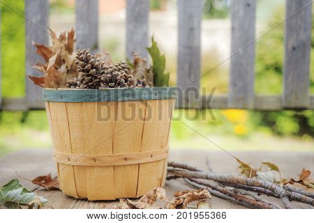 Autumn Bushel Filled With Pinecones And Leaves Sitting On Rustic Wooden Deck With Branches