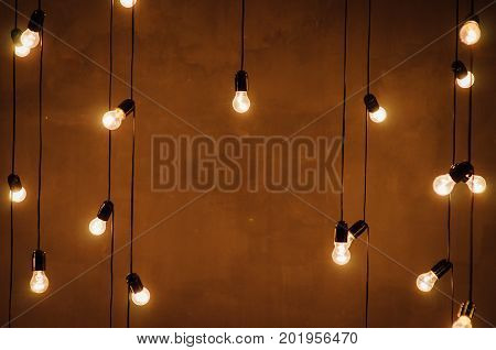 garland of edison lamps on a brown wooden background