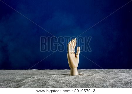 Wooden hand gesticulates on white sand and blue background