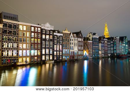 Amsterdam canal Singel with typical dutch houses and houseboats by night, Holland, Netherlands.