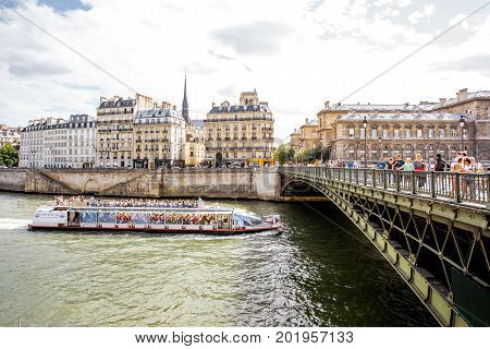 PARIS, FRANCE - August 07, 2017: View on the riverside with Arcole bridge and tourist boat in Paris
