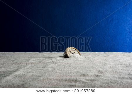 An old alarm clock on white sand and blue background