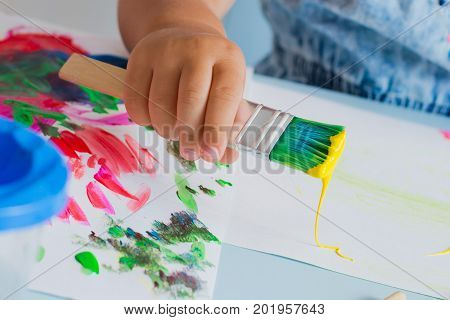 Brush with paint in the child's hand. Close-up