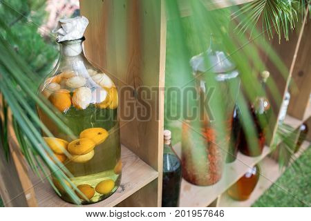 Tincture bottles of lemon, currant, berries and rowanberries. Herbal medicine. A strong alcoholic drink