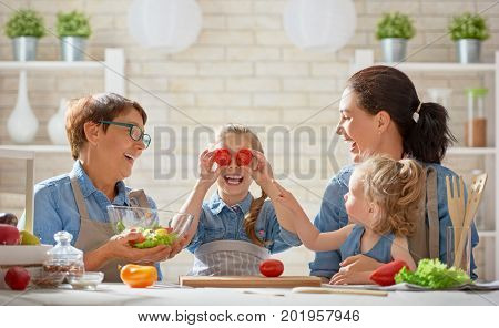 Healthy food at home. Happy family in the kitchen. Grandma, mother and children daughters are preparing the vegetables and fruit.