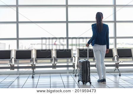 Travel tourist waiting at airport lounge with suitcase at tarmac window. Unrecognizable woman looking at lounge looking at airplanes while waiting for boarding gate before departure. Travel lifestyle.
