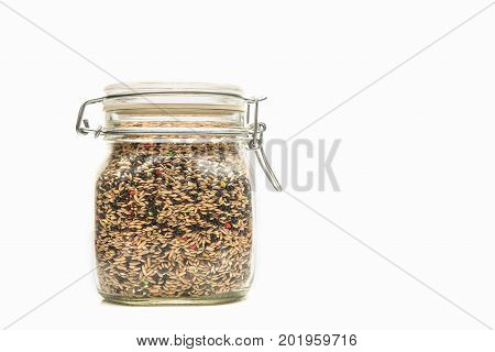 Glass jar with Mixed bird seed. Jar with a steel lock on a white background