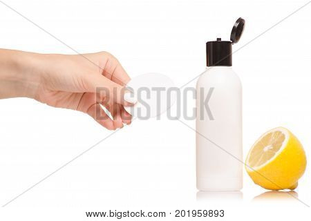 Female hand cosmetic with lemon wadded disk on white background isolation