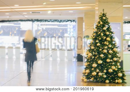 Abstract defocused motion blurred unrecognizable blond girl with long hair in the shopping center hurry to buy gifts for loved ones in the pre-Christmas holidays. For festive background , backdrop