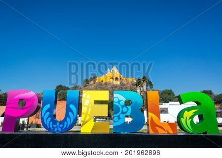 Puebla sign with Our Lady of Remedies on a hill in the background in Cholula Mexico