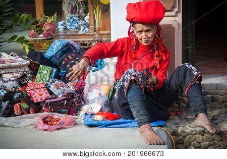 SA PA, VIETNAM - AUGUST 2017: Red dzao ethnic minority woman sewing in Sa Pa, Lao Cai province, Vietnam