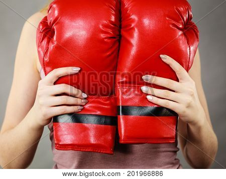 Unrecognizable sporty woman holding red boxing gloves. Studio shot on grey background.