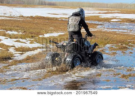 Youth quading through spring run off water