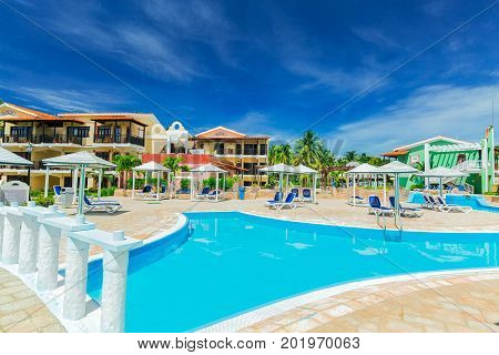 Cayo Coco island, Cuba, Colonial hotel, July 16, 2017, stunning gorgeous view of Colonial hotel grounds, beautiful inviting swimming pool and retro stylish buildings on dark deep blue sky background