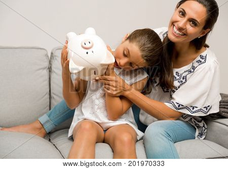 Mother and daughter with a piggy bank for her future savings