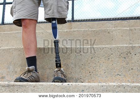 Standing man with prosthetic leg on concrete bleachers, wearing shorts