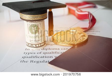 Concept of Success international education graduation black cap on roll up Dollars bill on letters diploma medals and passport for work and studying competition on abroad in famous institution.