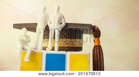 Miniature figurine sitting on rubik puzzle with Graduation cap Rubik's Cube is 3D combination puzzle invented Education international Concept