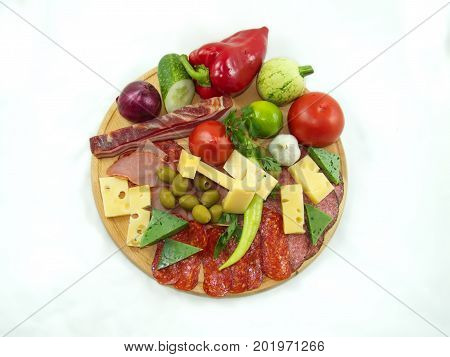 Vegetables fruits bacon prosciutto and cheese on round - wood cutting board.