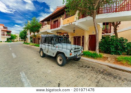Cayo Coco island, Cuba, Colonial resort, July 16, 2017, great inviting view of hotel grounds, stylish retro buildings with old vintage SUV truck parked on the road
