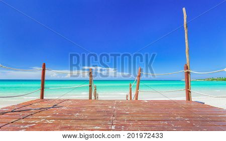 great amazing inviting view from a wooden deck, pier toward tropical white sand beach and tranquil turquoise ocean on blue sky background at Cayo Coco Cuban island, sunny summer beautiful day