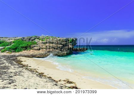 amazing inviting view on a cliff sitting in tranquil turquoise ocean and beach against blue sky magic background at Cayo Coco Cuban island on sunny summer day