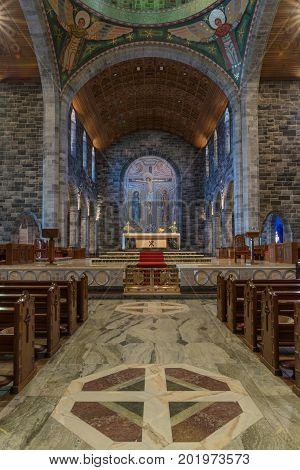 Galway Ireland - August 5 2017: Chancel sanctuary with altar on marble floor with Crucifixion backdrop seen from nave. Colorful combination of floors walls ceilings and part of dome support structure.