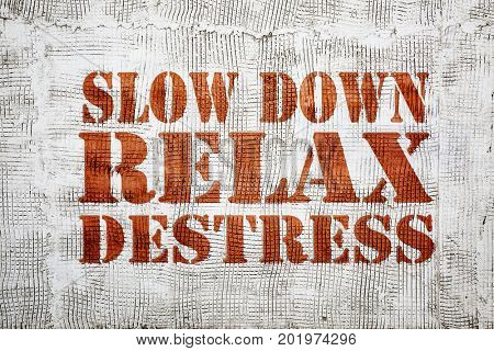 slow down, relax and destress - graffiti sign on a stucco wall
