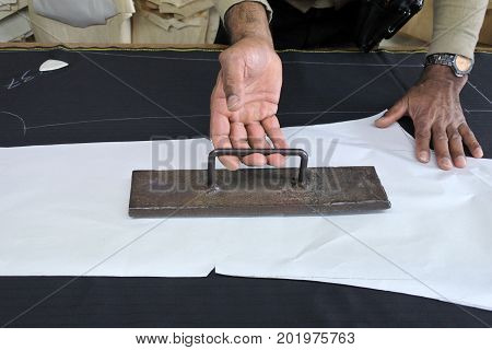 Hands Of A Tailor Placing A Weight Over Measurements