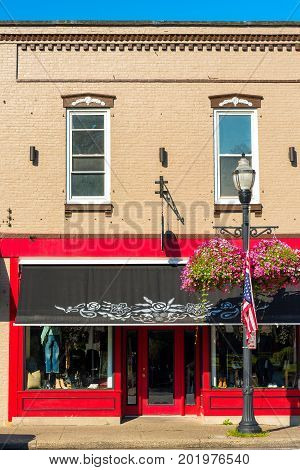CHAGRIN FALLS OH - JULY 30 2017: A clothing storefront with a bright red facade and decorative awning adds to the charm of this Northeast Ohio village.