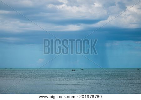Fishing vessel under storm with big waves in storm and raining. Dark rainy clouds over tropical sea. Sea landscape with bad weather and the cloudy sky.
