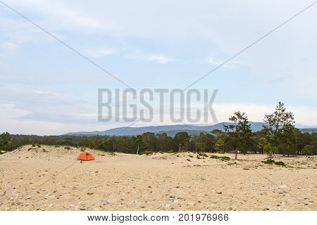 Tourist tent on the sandy beach of the shore of Lake Baikal in Siberia in the summer among coniferous trees on a mountain background.
