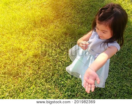 Cute Asian girl in beautiful dress stand on green field.Adorable kid play alone in the park.Pretty girl and happiness time.