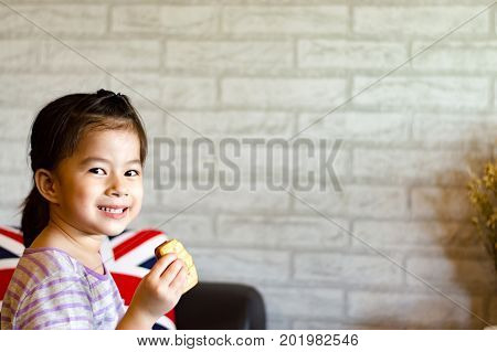 Little girl with smile face selective focus.Cute asian girl and snack time,with copy space.