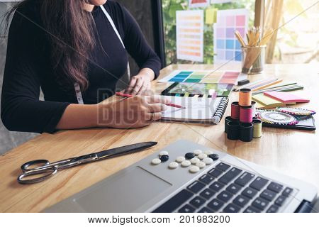 Young woman dressmaker or designer working as fashion designers and drawing sketches for clothes and choose color bar in tablet profession and job occupation Fashion Designer Stylish Concept. poster