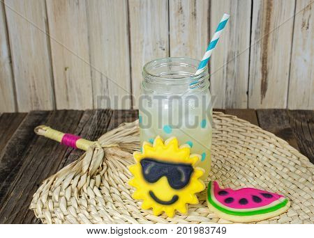 sun and watermelon sugar cookie with lemonade drink in mason jar on bamboo place mat