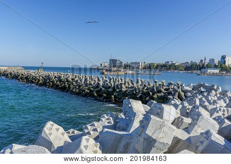 Bay view of the port town of Tomis, Constanta. Tetra-pods or concrete breakwater blocks at Tomis, Constanta harbur. Sea wall for protect the beach. Breakwaters concrete tetra-pods.
