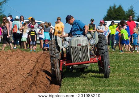 DUNDAS, PRINCE EDWARD ISLAND, CANADA - 25 Aug: Competitor plows with antique tractor while spectators look on at the PEI Plowing Match & Agricultural fair on August 25, 2017 in Dundas, PEI.