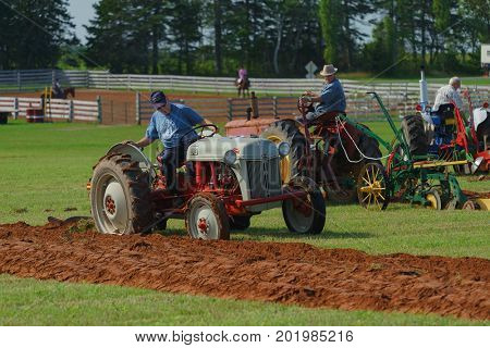 DUNDAS, PRINCE EDWARD ISLAND, CANADA - 25 Aug: Competitors plow with antique tractors at the PEI Plowing Match and Agricultural fair on August 25, 2017 in Dundas, Prince Edward Island.