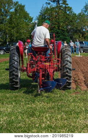 DUNDAS, PRINCE EDWARD ISLAND, CANADA - 25 Aug: Competitor plows with antique tractor while spectators look on at the PEI Plowing Match and Agricultural fair on August 25, 2017 in Dundas, PPEI.