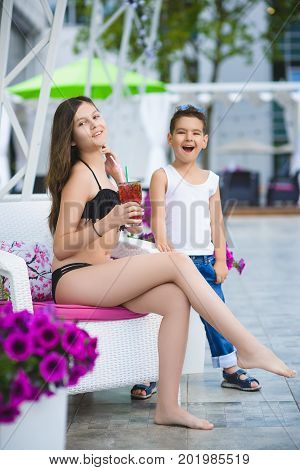 teenage girl and smiling girl relaxing on a lounger outdoors.