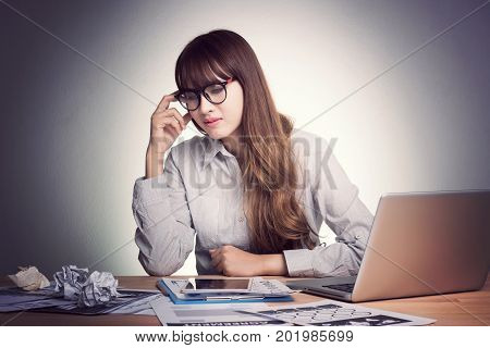 Feeling tired and stress. A stressed Asian business woman looks tired in her office