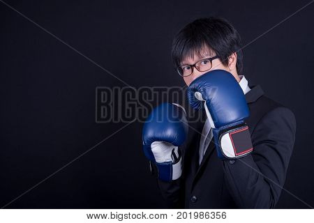 young asian business man wearing suit and posing with blue boxing gloves in black background studio. business man fight pose concept