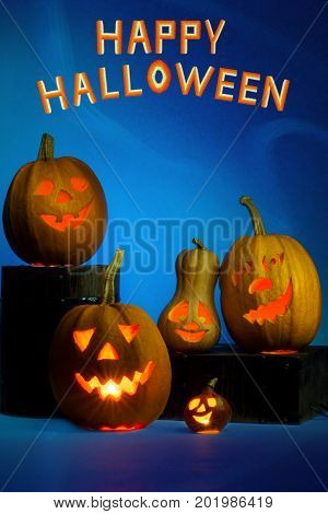 Happy Halloween pumpkin with a candlestick, funny face face on a blue background