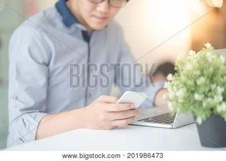 Young Asian business man dressed in casual style working in coffee shop with his laptop computer and smart phone. Digital nomad and IT modern lifestyle work life balance concept