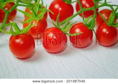 Fresh cherry tomato on rustic wood table. Close up lovely cherry tomato for background or wallpaper. Prepare fresh cherry tomato for home cooking look so delicious. Macro concept with copy space. Fresh cherry tomato on white wood table.