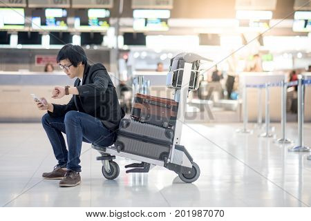 Young Asian man checking time sitting on airport trolley with his suitcase luggage in the international airport terminal business travel and flight delayed concepts