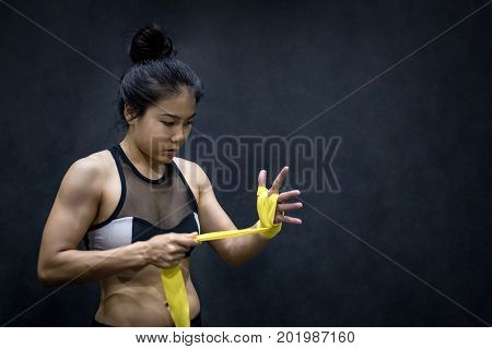 Asian female boxer wearing yellow strap on wrist. Beautiful young woman with muscular body preparing for boxing