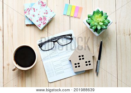 Business, finance, savings, property ladder or mortgage loan concept : Top view or flat lay of saving account passbook or financial statement, wood house model, and accessories on wooden background