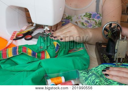 designer making a garment in her workplace. seamstress sews clothes. Workplace of tailor - sewing machine rolls of thread fabric scissors. sewing machine and female scissors